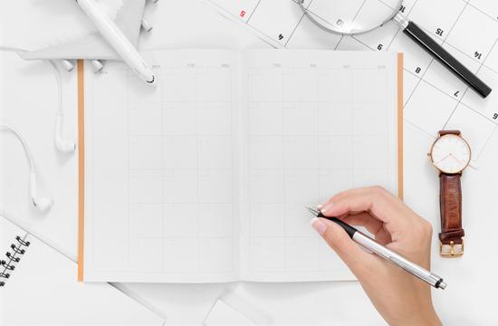 女性がスケジュール帳を開いて書き込もうとしている写真