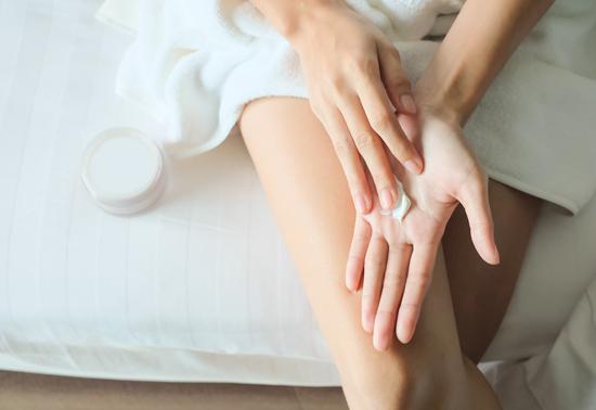 手にハンドクリームを塗り込んでいる女性の写真
