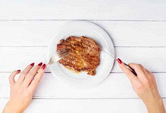 肉を食べている女性の手元の写真