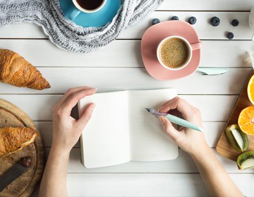 女性がノートに何かを書いている画像