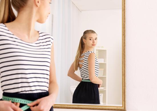 女性が鏡の前で身だしなみをチェックしている写真