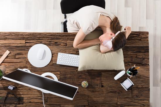 アイマスク・昼寝用枕を着用して昼寝している女性の写真