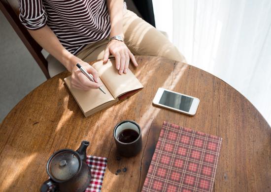 女性が日記にモヤモヤを書き出している写真