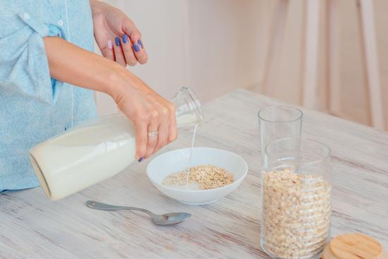 女性がオートミールに牛乳をかけている画像