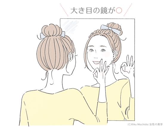 大き目の鏡でメイクをしている女性